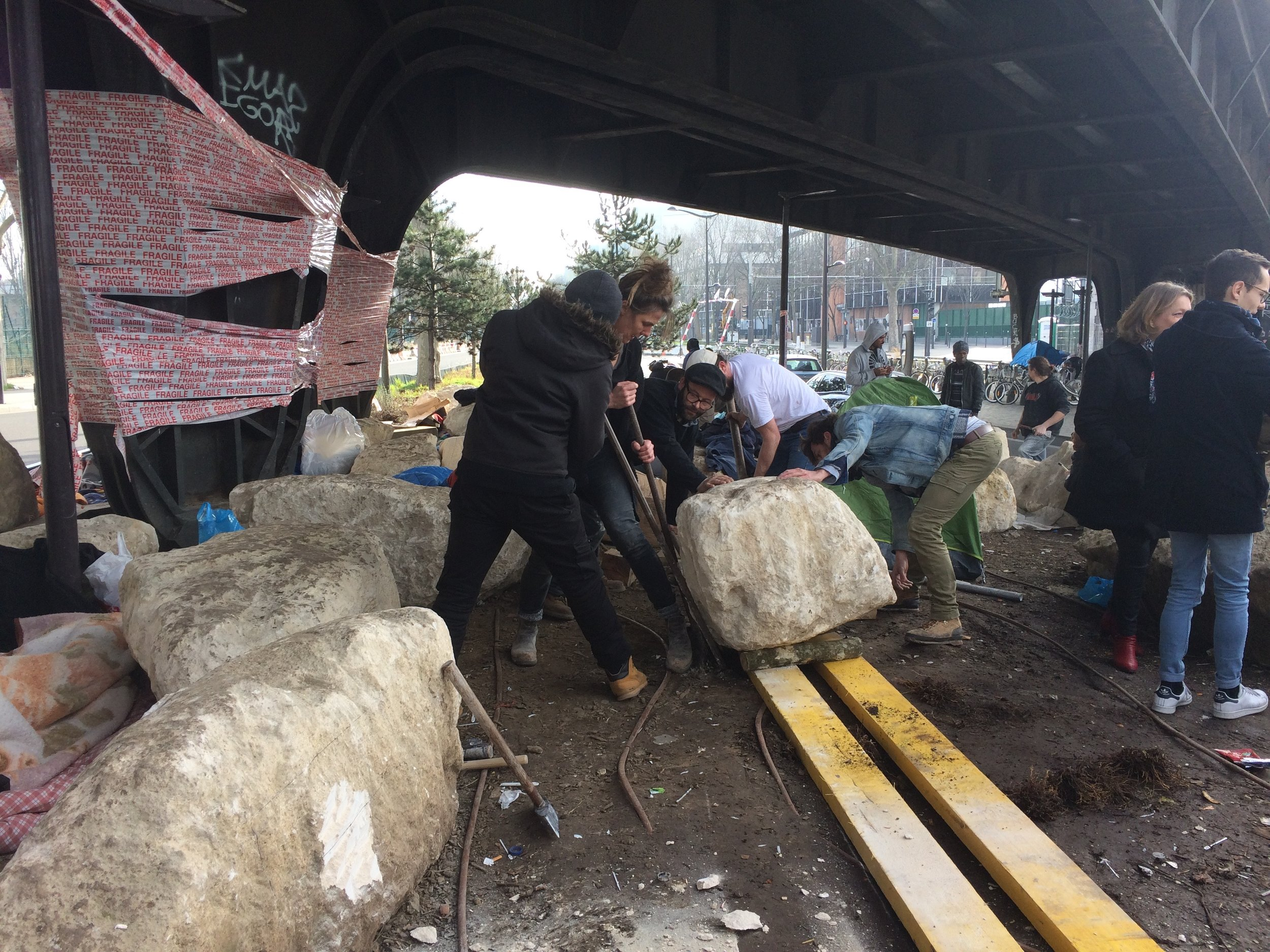 Preparing to move the boulder in order to create space for refugees to sleep.  © Lara Bullens