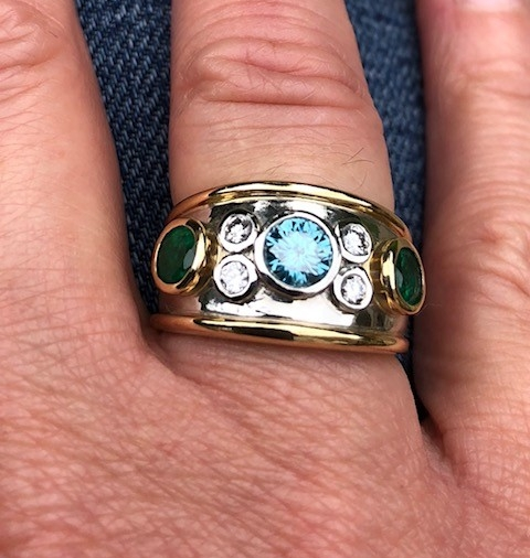 """The Fabulous Bombé Ring   """"I wanted something a little different and wow! This piece is definitely that. Chris designed me an amazing bombe ring, with a few of my own diamonds. He sourced some beautiful emeralds and a blue diamond, something I have never seen before. This is one stunning ring and I love it!  Chris is very personable and makes everything from start to finish special. He is truly brilliant at what he does and I can't thank him enough for this special ring.  Bespoke is Chris' speciality. I now have a one-off piece to be treasured and enjoyed every day.  Thank you so very much."""" - Mrs Beaumont, Wakefield."""
