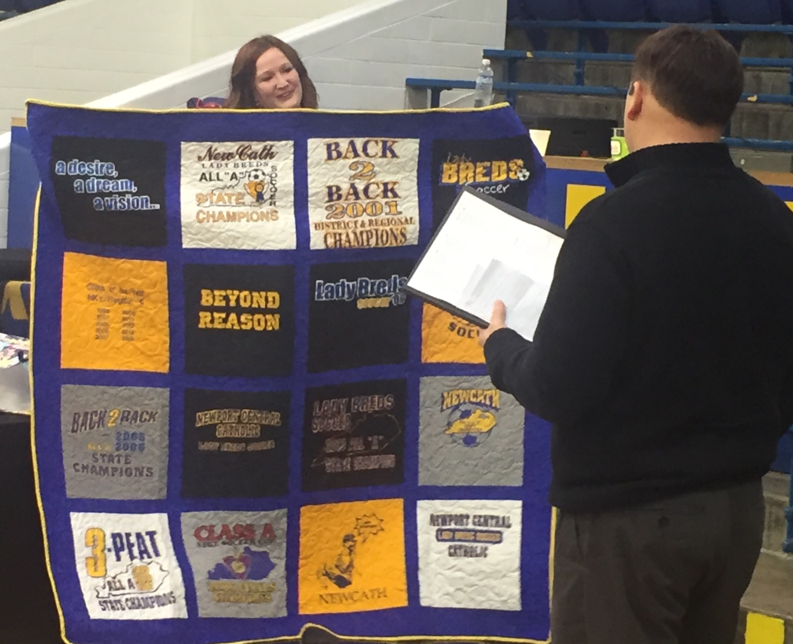 TEAMS of Distinction present Coach Kevin Turnick with a memory quilt of success history.