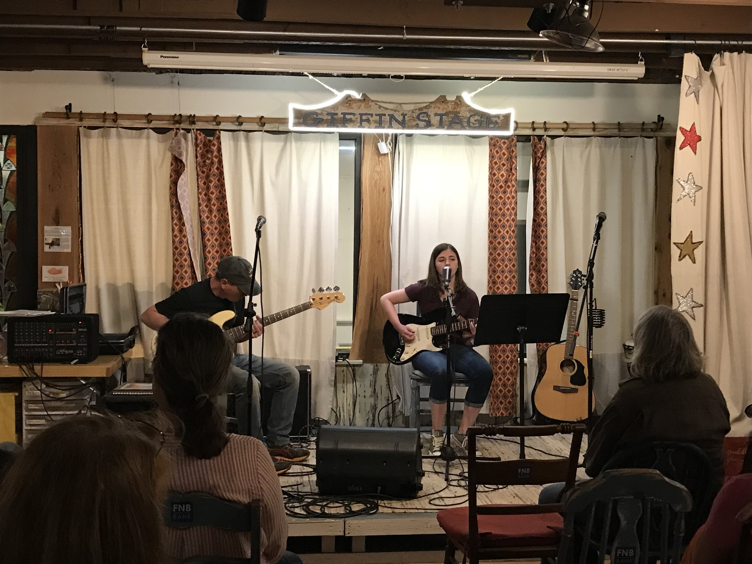 """Here's more about our high-school performer, a talented musician who has played at Open Mic Night:  """"I'm Olivia Chisholm, from Capon Bridge, WV and I'm 17 years old. I perform with my dad, who has played bass for 30+ years. I play guitar with him, as well as for my school jazz band. My musical style ranges from classic rock, alternative rock, and metal. Although I have several influences, the ones that come to mind are Stevie Nicks, Led Zeppelin, Red Hot Chili Peppers, and Mark Tremonti."""""""