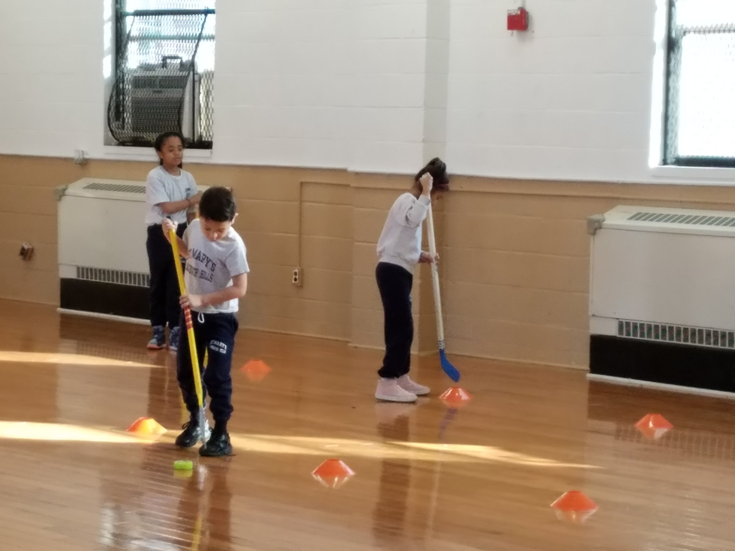 Second Grade practicing their hockey dribbling skills.