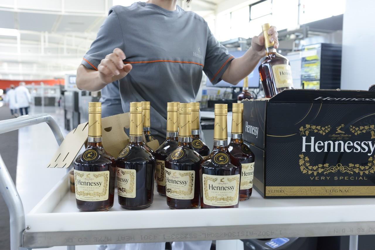 Bottles pass through a series of machines where they are filled with cognac, labeled and then packaged in twelve-bottle boxes.  JULIEN FERNANDEZ FOR THE WALL STREET JOURNAL