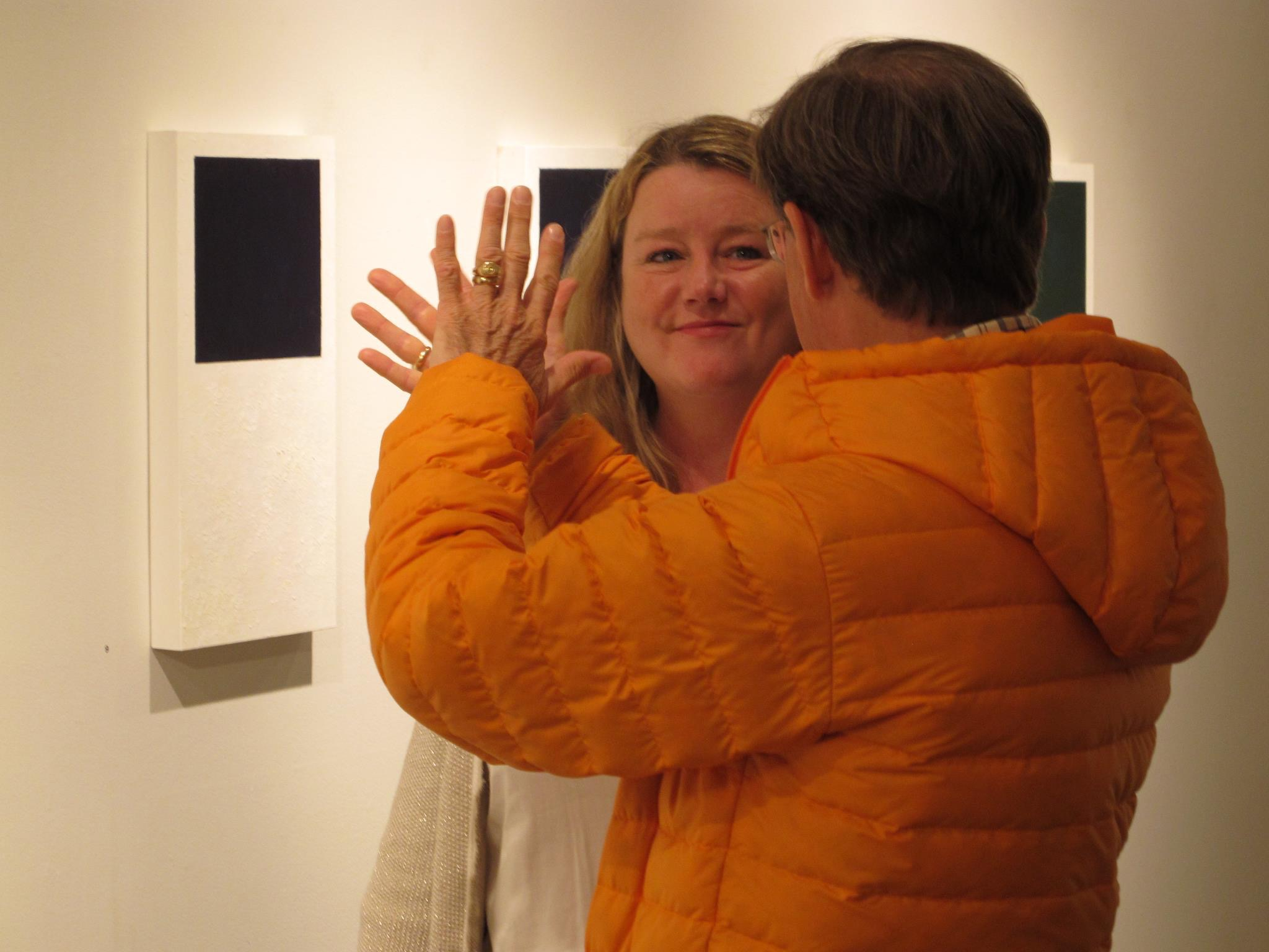 """Joanie visiting with a friend during the opening of her """"Windows"""" exhibit at Iowa Contemporary Art Gallery."""