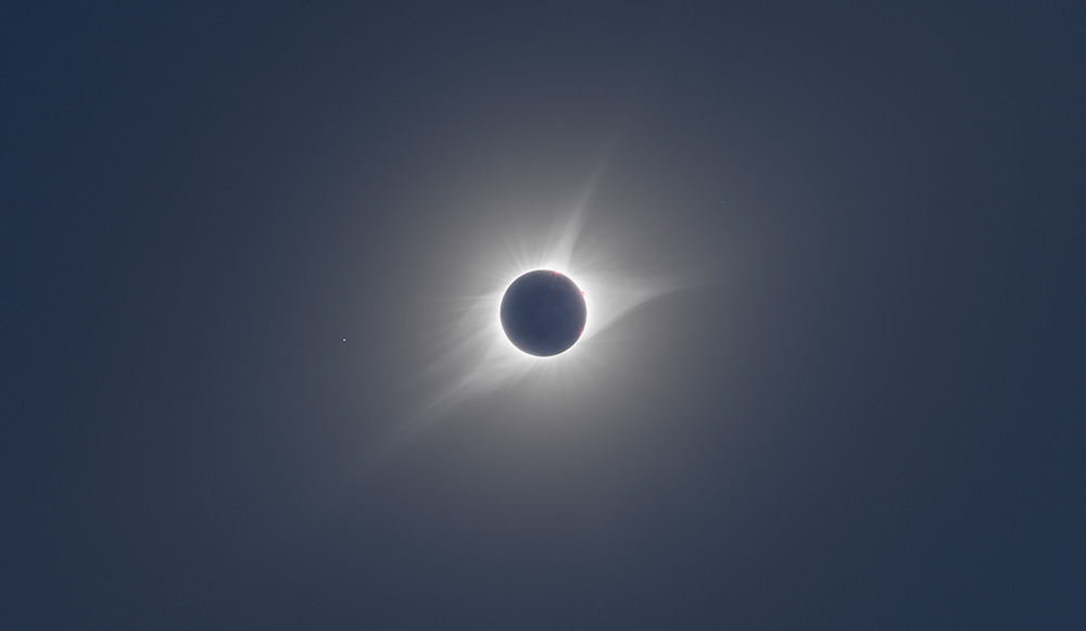 This is the most true-to-life image of the total solar eclipse I could find online. Just imagine the sky a little lighter, and the corona eerily waving around, and you're  nearly  there. Image credit:  Conrad Pope .