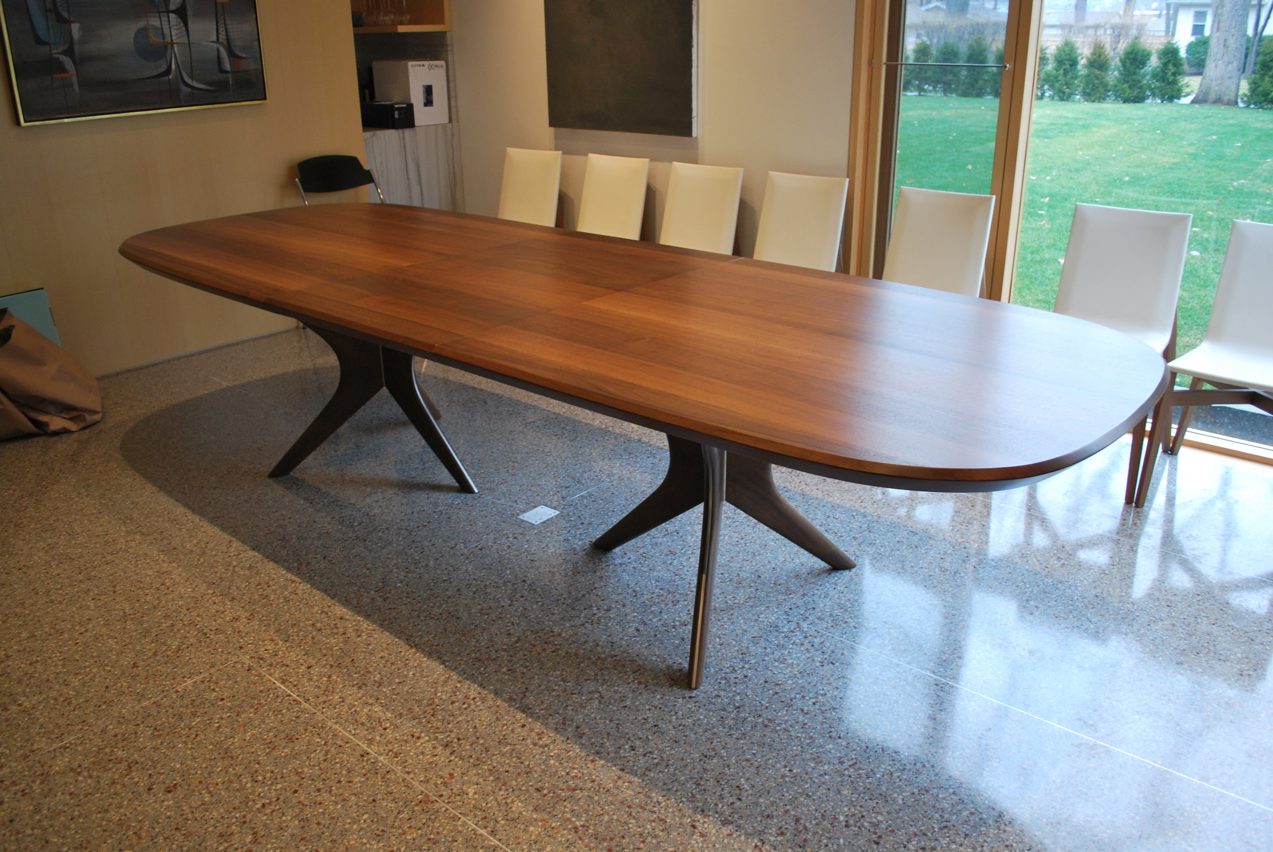 Double Tripod Extension Table   Solid black walnut dining table with stainless steel accents on pedestal bases.