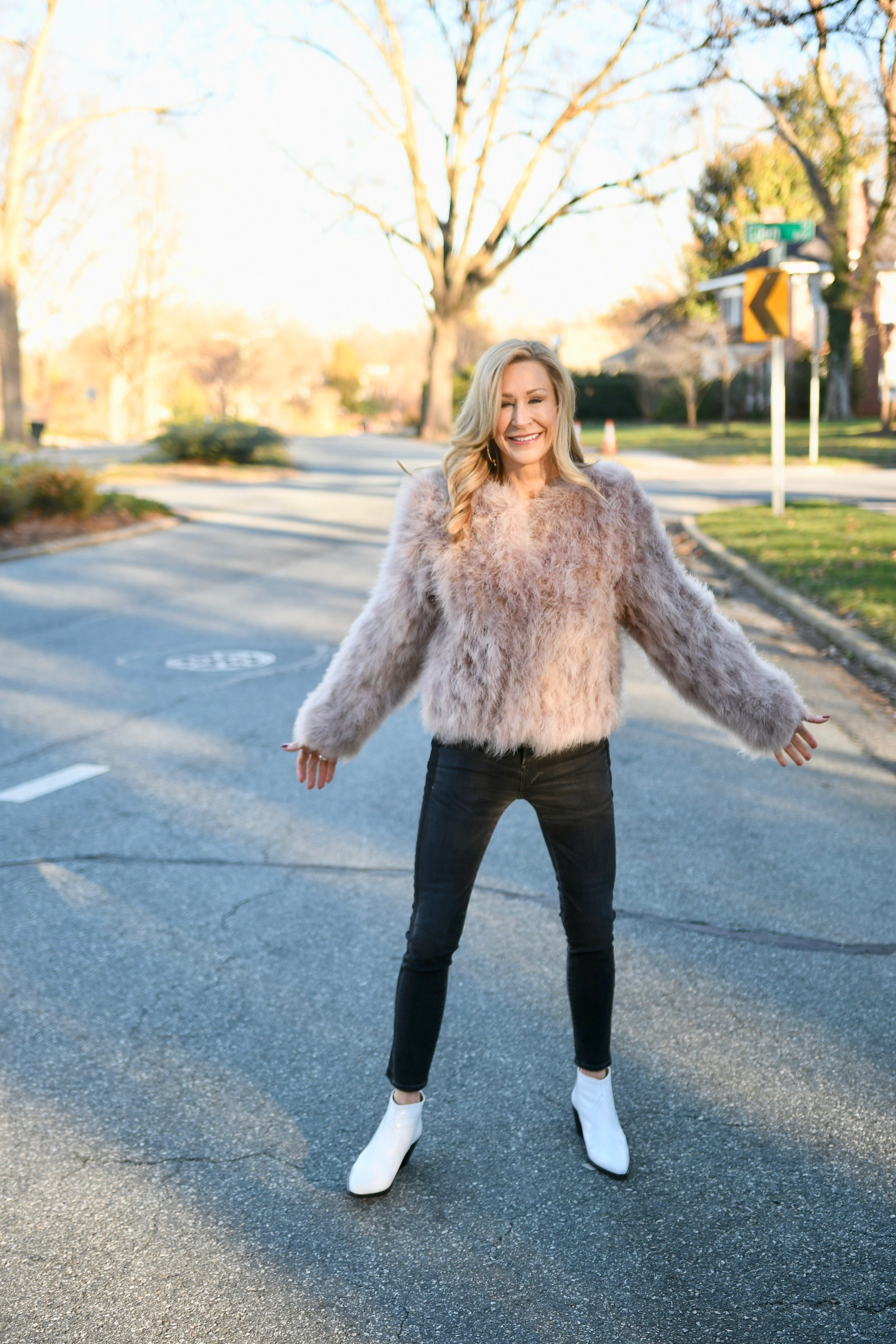 Pink fur with black jeans and white cowboy booties