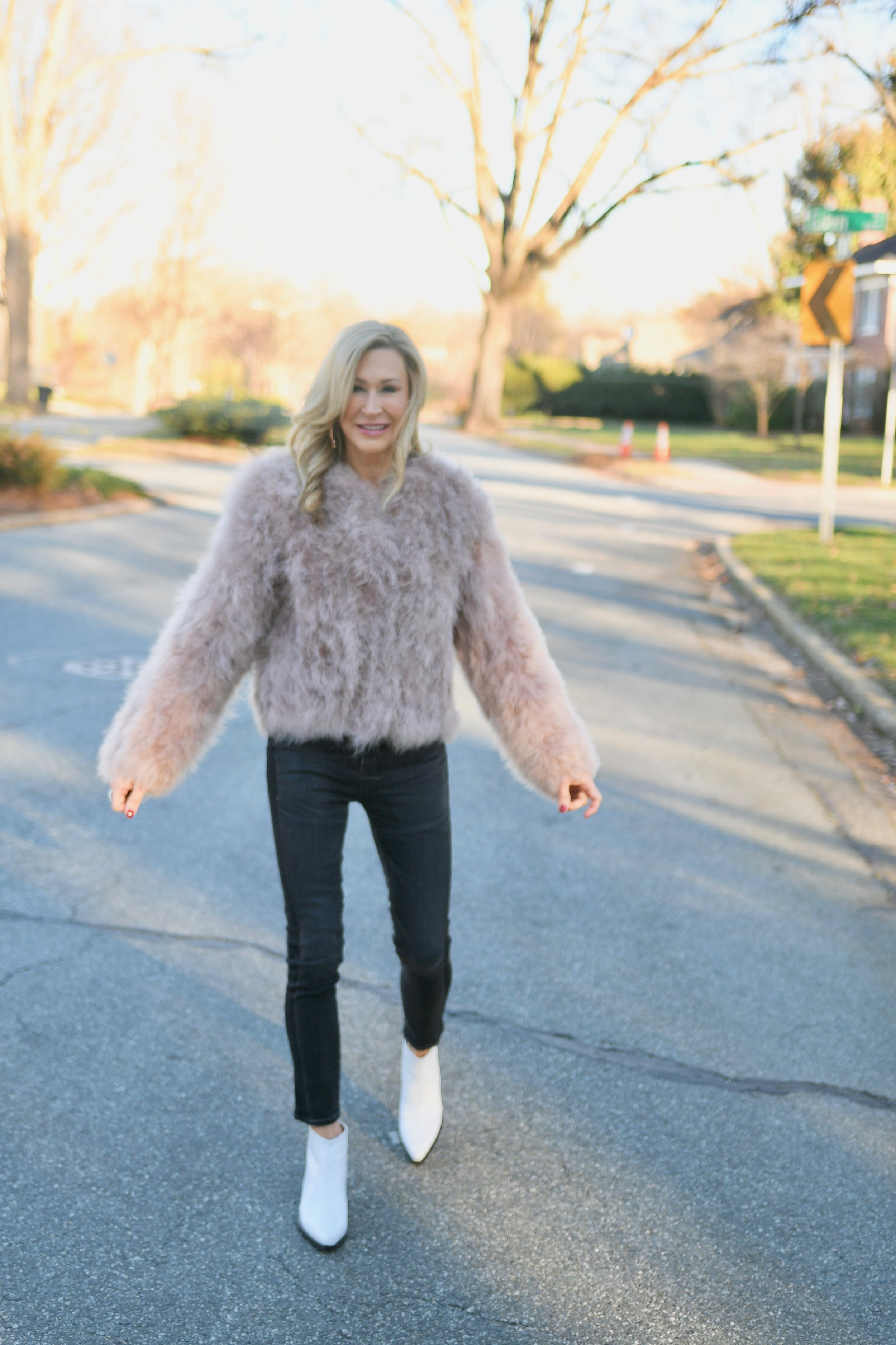 Pink fur coat with black jeans and white cowboy booties