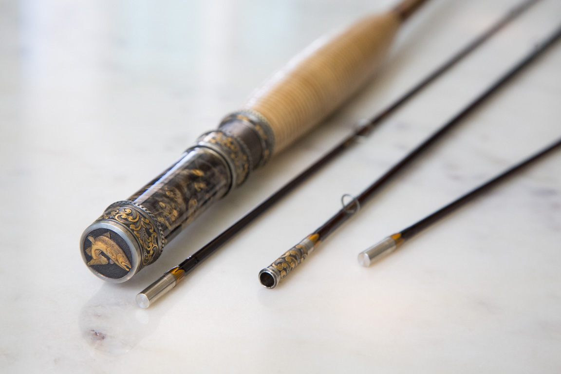 An Oyster Bamboo Fly Rod with intricate hand-carved engravings.