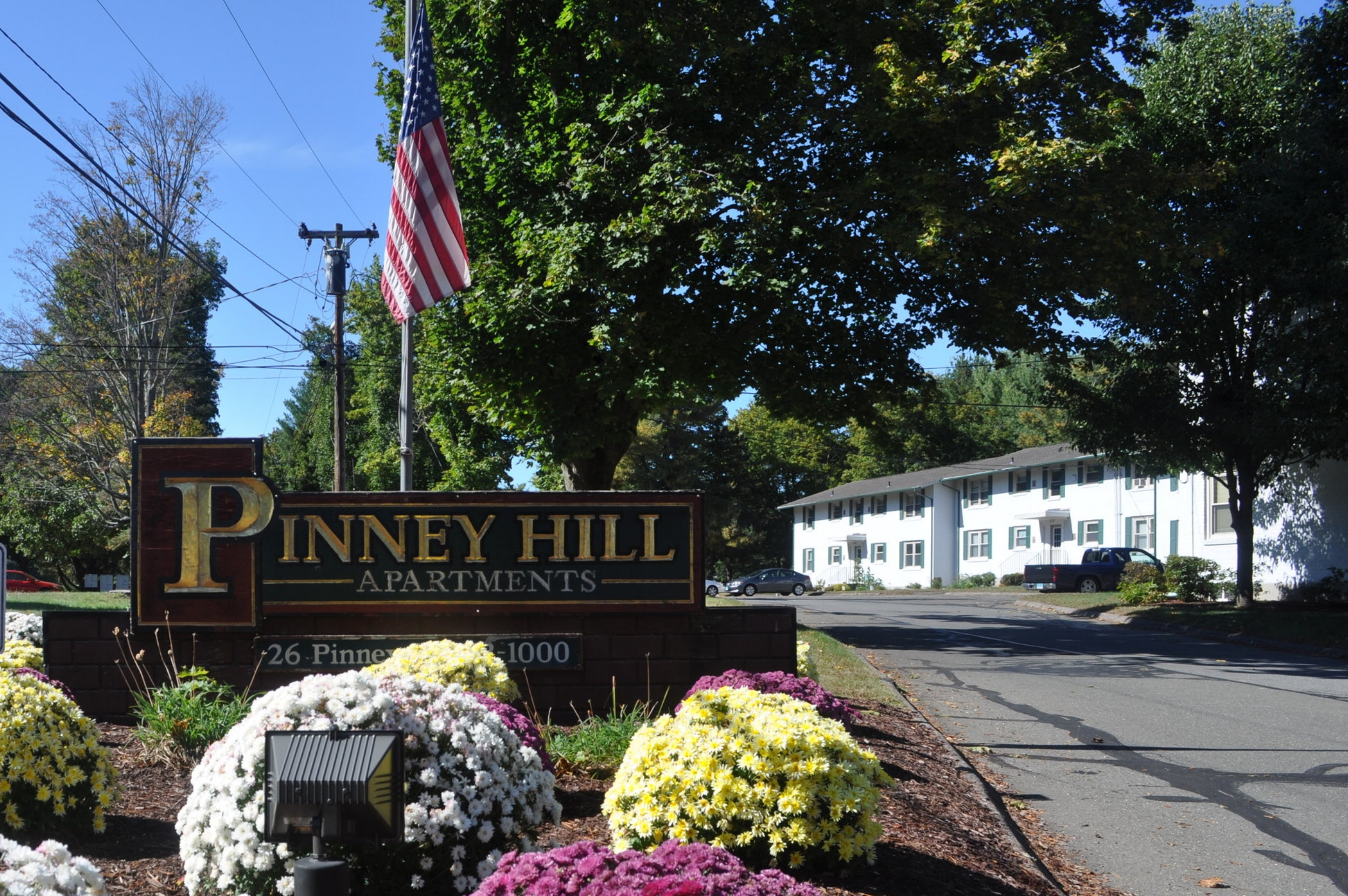 Pinney Hill property sign with flowers in front and an American Flag pole in back with a white building with green shutters to the side with trees all around.