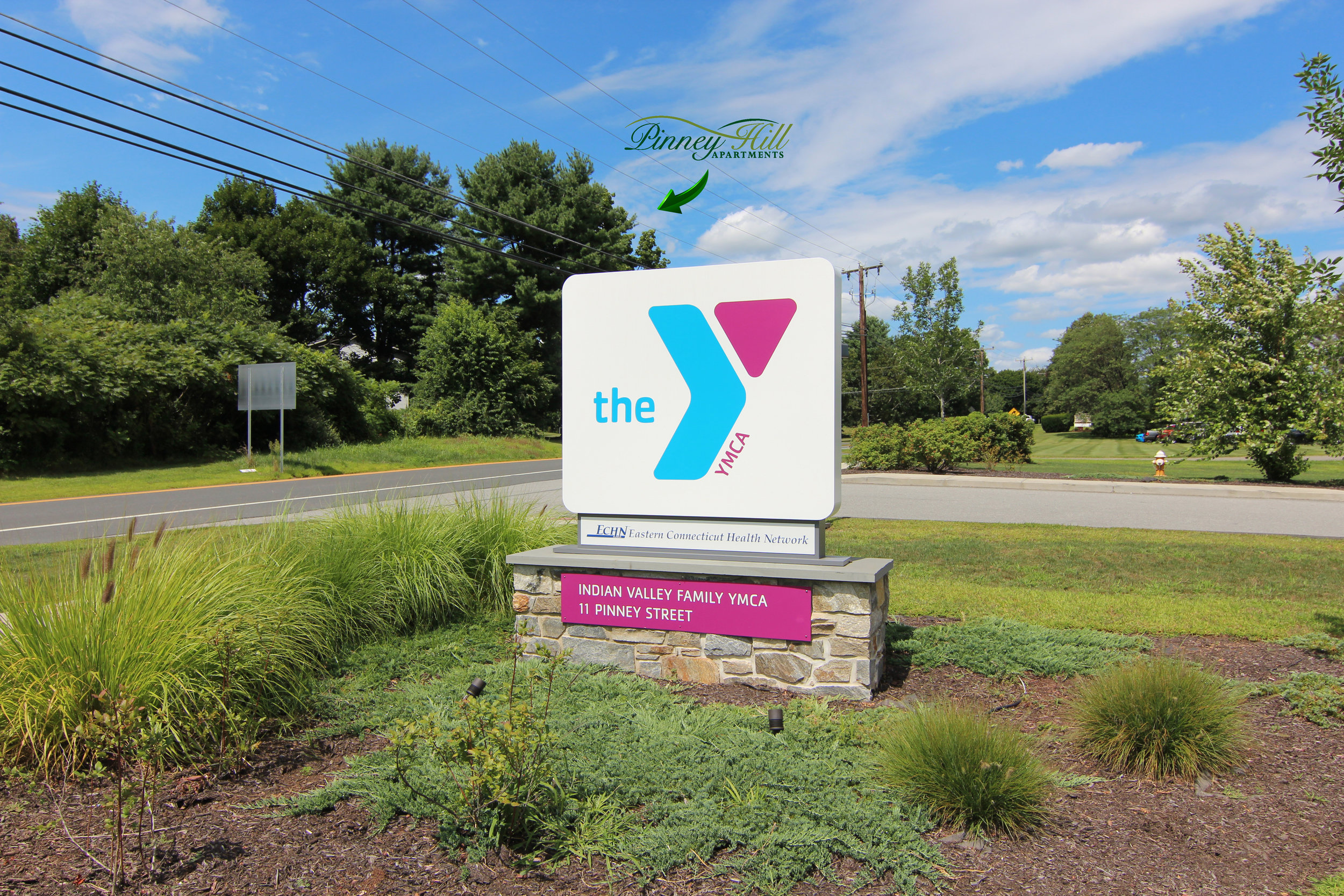 Image of the local YMCA sign with an arrow pointing to trees where Pinney Hill is located across the street.