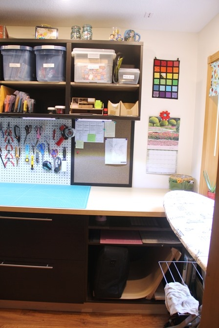 Corkboards and pegboard over sewing workspace
