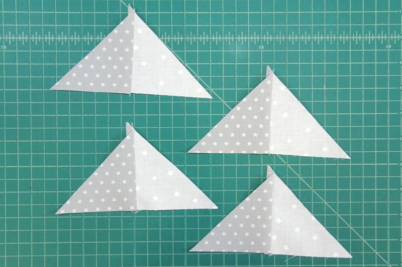 Grey and white pieces sewn for pinwheel square mini quilt