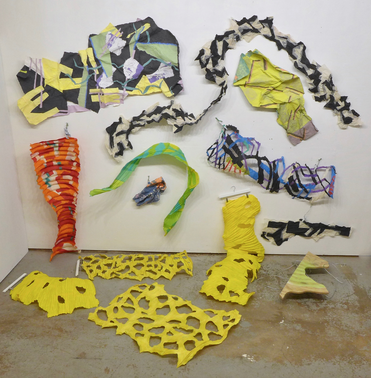 """The yellow shapes are cast on HVAC ducting except the foreground one which was cast from a large trash can wrapped with thick fencing wire (below left). Ribs give the pieces some structure and volume. We put the holes in when we're casting.    The black and white """"scarf"""" is just shapes of abaca fitted together. It was made flat, but U shaped to give it some twist and bulk even when used more or less straightened."""