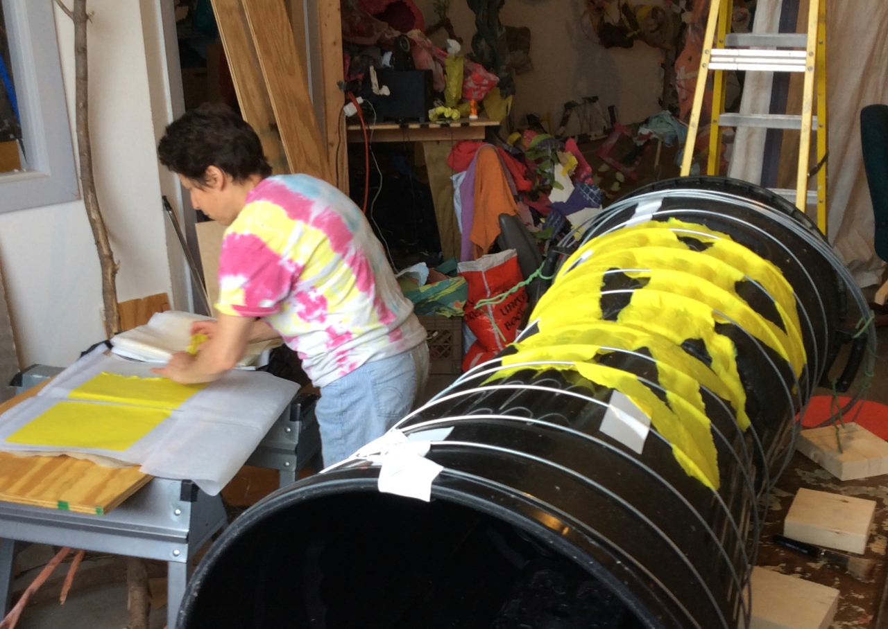 """Trash cans taped bottom to bottom are used to create a form to cast abaca. The heavy wire around the cans provides the piece with structural ribs. The """"yellow jackets"""" are built up from strips of abaca rather than full sheets to give a more interesting look when seen through transmitted light and to give greater tear strength."""