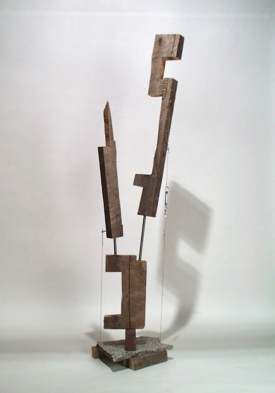 """The material suggests what to do and it responds and then it suggests again. The wood was once a single squared off length. I cut some rectangles out of it unmindful of the deep longitudinal cracks. Some threaded rod might be a way to """"repair"""" the wood, but the rod worked better as a way to accentuate the brokenness. To use the piece of stone counter top as a base required some epoxy. That'd be too final for second thoughts so cabling the wood to the base. The cable seems to pull the wood pieces outward while the wood seems to pull the base upward. There were no second thoughts."""