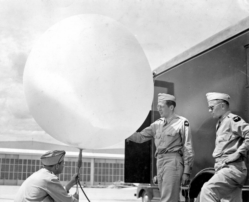 """In 1940, Rossby left the US Weather Bureau to establish an Institute of Meteorology at the University of Chicago. There he organized the program that trained the  weather cadet generation : more than 6,000 new weather officers for the US military. George Benton described this as the """"explosion in meteorology."""" Here,three cadets at Chicago practice filling a weather balloon.  Image courtesy of the University of Chicago Photographic Archive, apf3-02893, Special Collections Research Center, University of Chicago Library."""