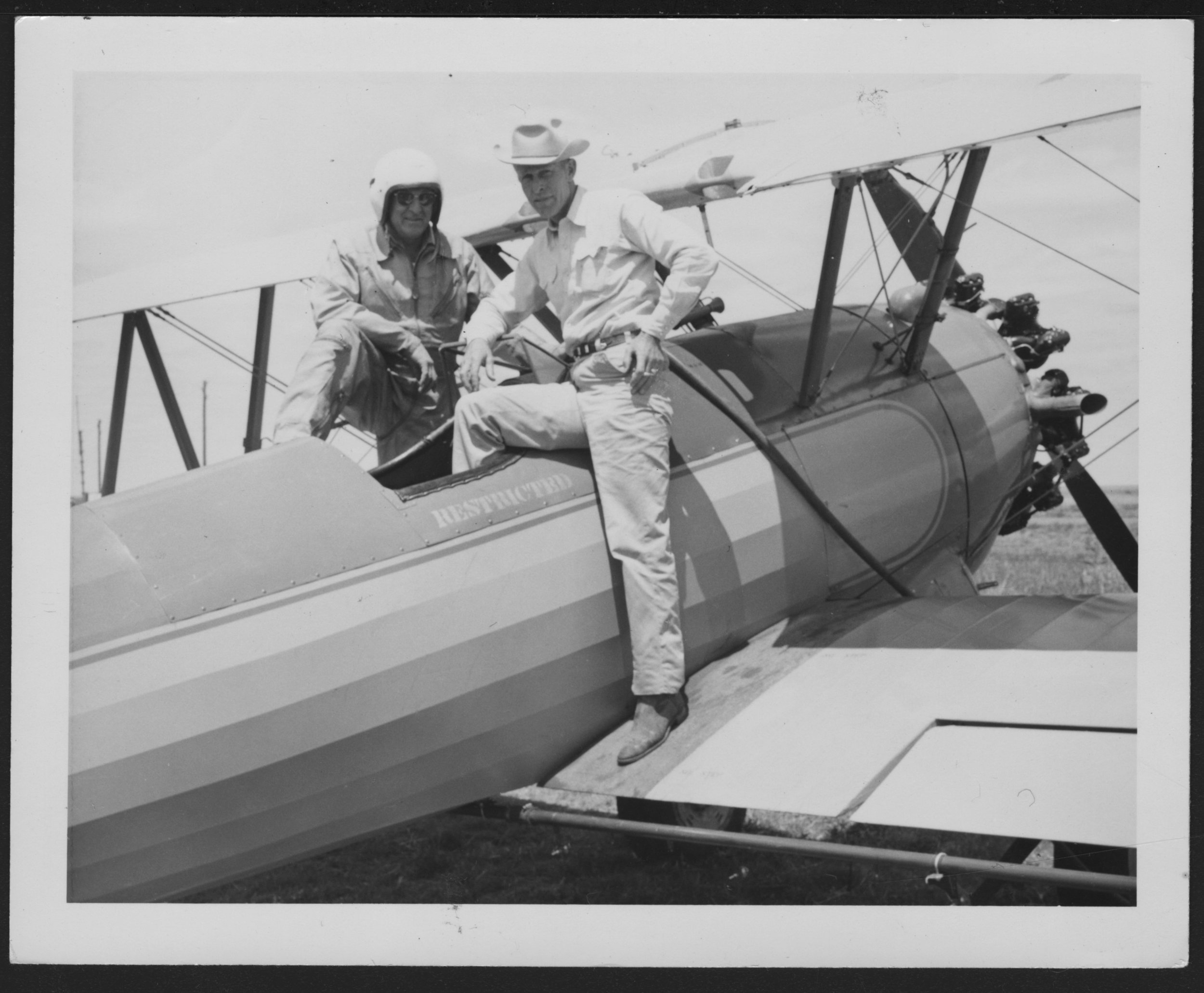 Grassland Ag pilots and weed scientists often worked together to address agricultural perils involved with pesticides and mitigate risks. In this late 1950s photograph, Dodge City spray pilot Roy Mahon can be seen in discussion with local weed supervisor Ralph Strum, who stands on the plane's wing. Courtesy of the Kansas State Historical Society.