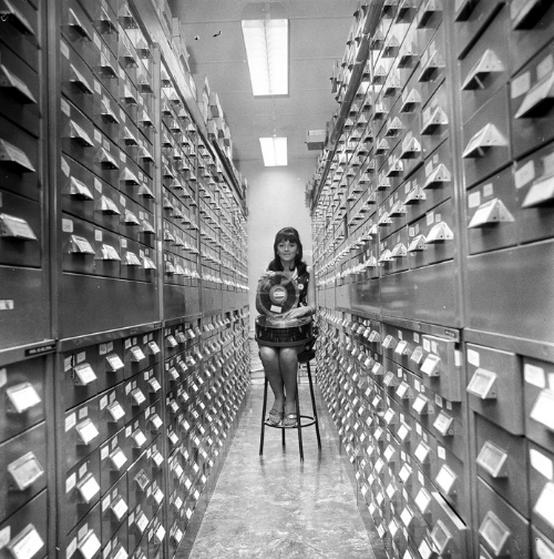 """""""A girl holding a decade of Australian weather records in her hand on a modern-type magnetic disc storage unit,"""" 1970.Produced by the Australian News and Information Bureau, via the  National Archives of Australia ."""