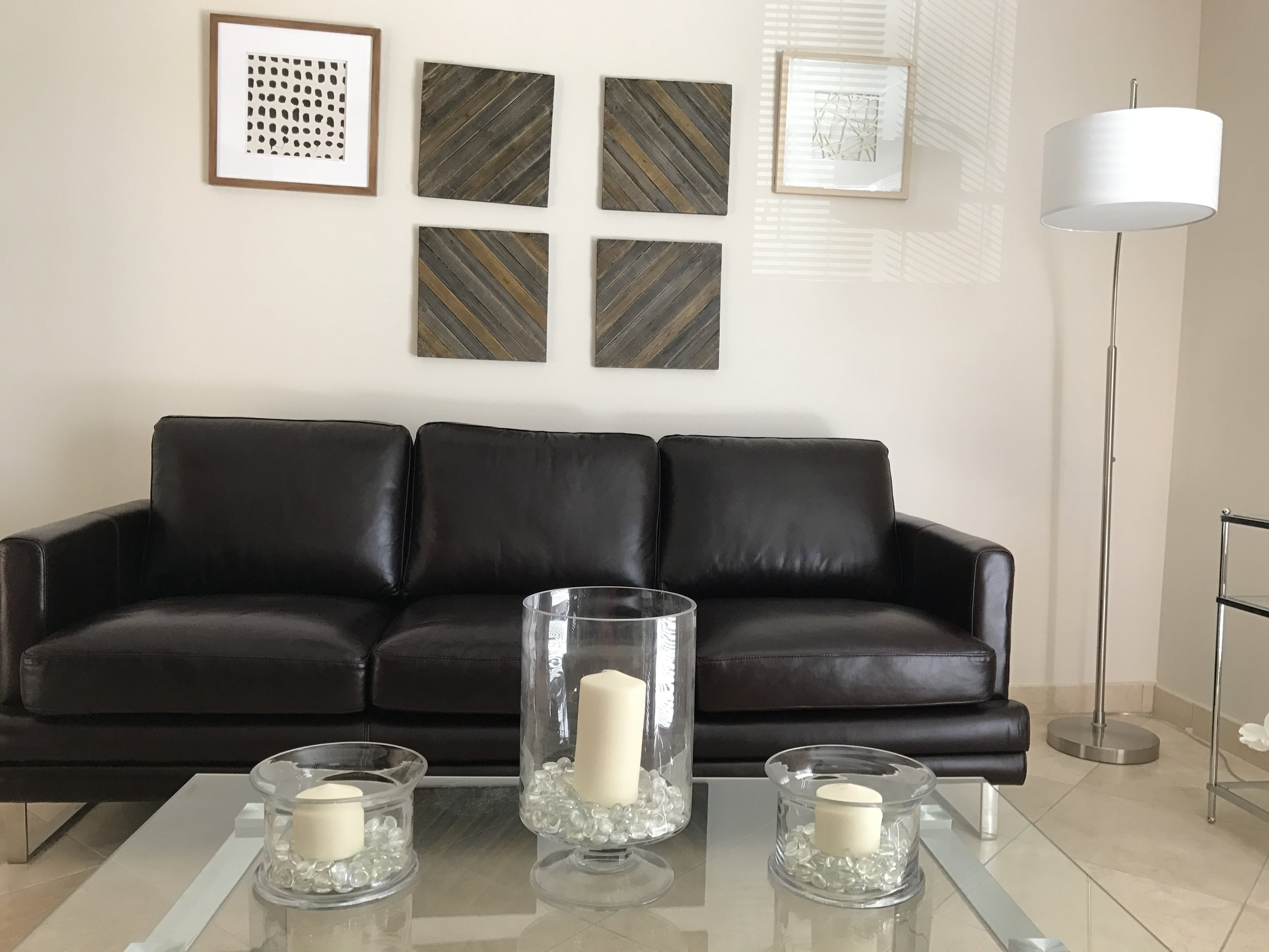 Table with candles in front of couch and wall art