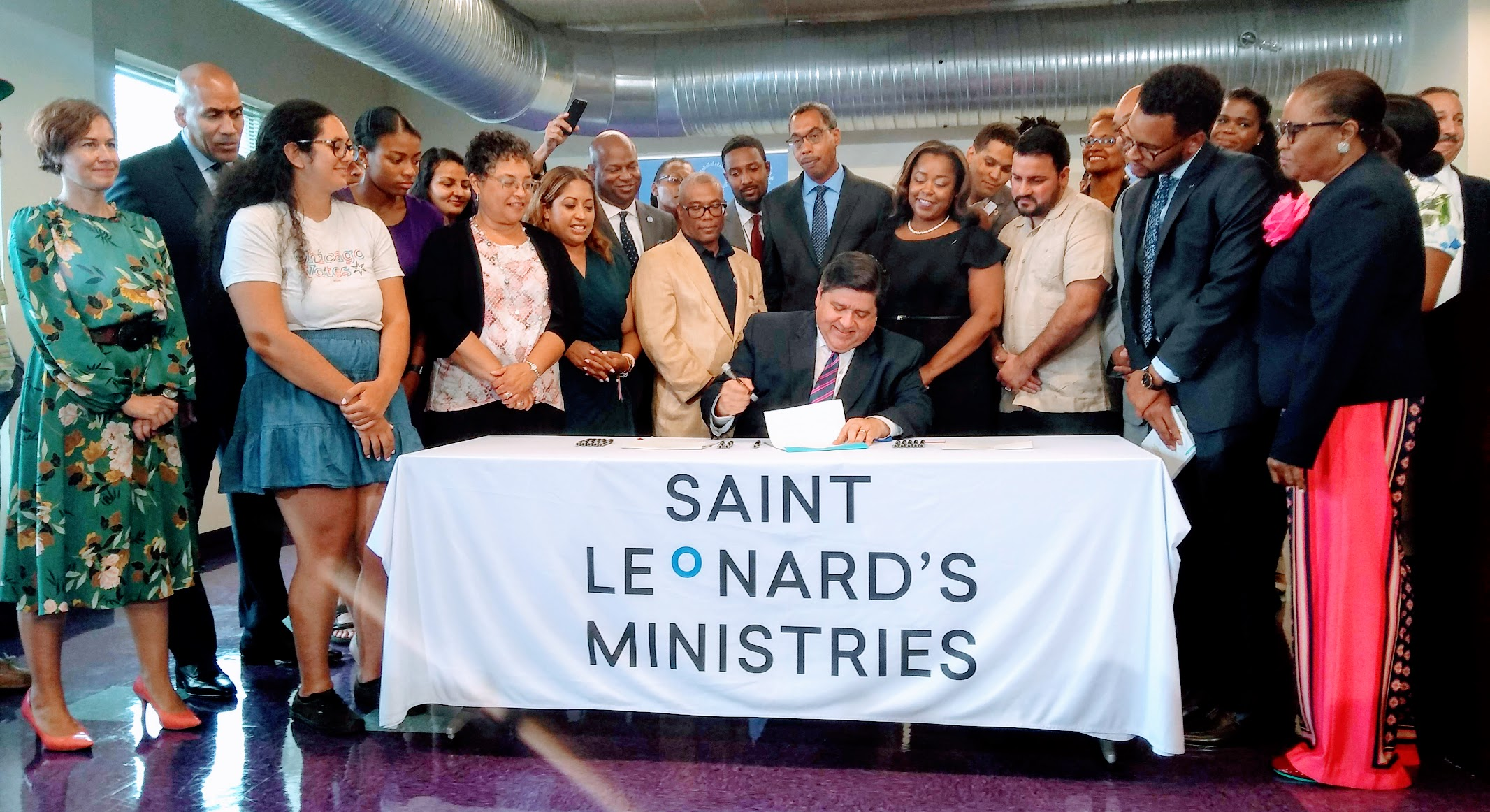 Governor J.B. Pritzker and advocates at the Reentering Citizens Civic Education Act signing ceremony.