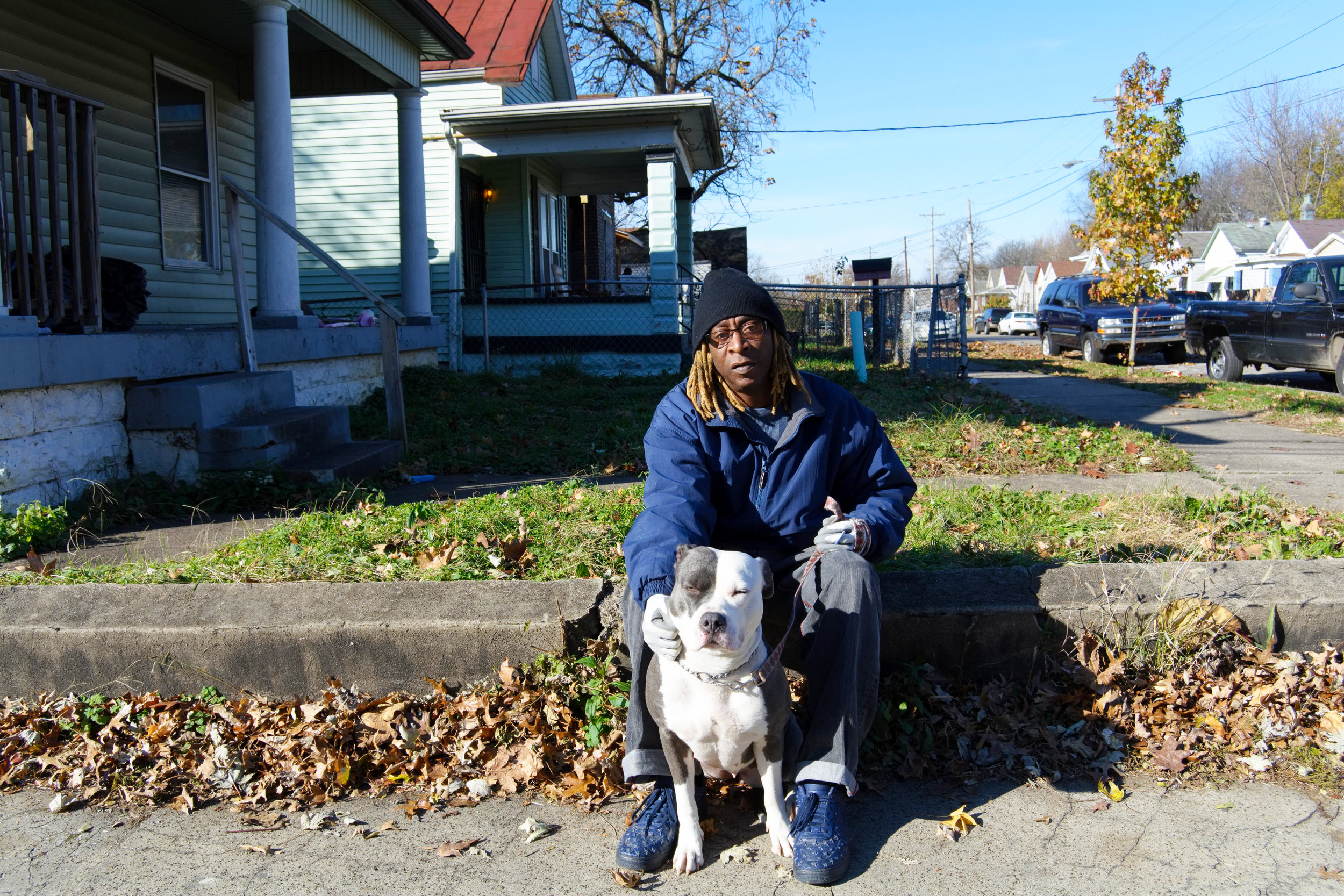 """""""I'ma keep it real with you. I just got back into God. I got three girls. Out of my three girls, my oldest one is still living. When I was living in Baltimore, one of my girls was 7 years old and got shot in the head. I came back to Louisville and my 16-year-old got shot in the head. My 40-year-old came back from Alaska and now she lives in Houston. I got four grandkids. I turned 60 on Friday and for a long time, I had doubts about God. You know, I lost my two girls, my father died in my arms and came back to Louisville and my grandmother died. I finally got to meet my mother, whom I didn't know for 25 years. I couldn't say that I loved her or liked her, and she died. I also had a sister that jumped off the bridge, so I had a lot of tragedy. I'ma keep it real with you. I was diagnosed with depression and suicidal, I get SSI. I had three suicide attempts, but for some reason, he's holding me here. I'm just keeping it real with you, it's my life story.  Now, 12 years clean and sober, I don't do anything but walk this girl (points to the dog), that ain't mine. I stay with my sister, who is 20 years clean and sober. On April 7th, next year, I'll be 13 years clean and sober. I had a messed up life. Now, I'm getting God back into my life. I still have questions and doubts, but that's understandable, with everything that I've been through. For me, staying with my sister and my aunt helps me. I ain't been going to church every Sunday, but I go. As far as knowing the Bible, I don't know it but I'm getting to it. I'm dyslexic, but I'm teaching myself to get through it.  My oldest daughter came back to life and that motivates me. I abandoned her, in the past. When I graduated from Drug Court, she was the only one that was there for me. She came all the way from Alaska for my graduation. As long as I talk to her once a week, I'm good. I don't associate with too many people. I walk her. She's a good therapy dog. She's not mean to anybody. This is my buddy.  Be patient, things wi"""
