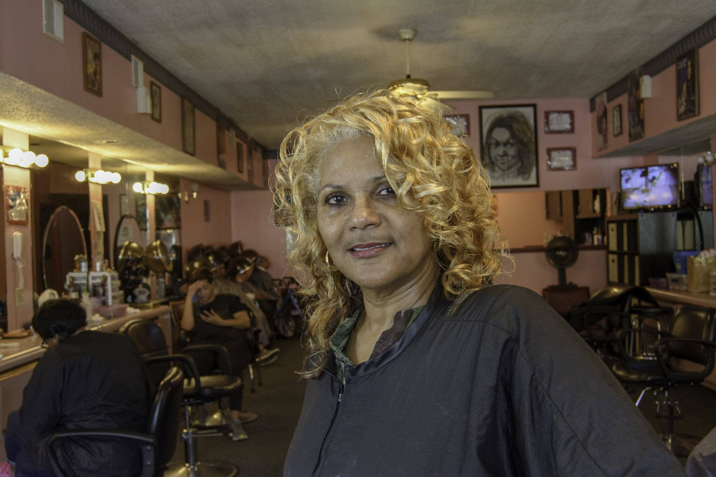 """""""I used to braid a lot children's hair, when their mothers couldn't. I would braid their hair for money, so I could go to Ghost Town, on the river. I'd go to Ghost Town or the skating rink. That's what really started it. I was 8 or 9, braiding hair. I would do that to get some money and go to the amusement park.  What really got me started was when I was in high school. We had to do a co-op. My first job was a job in the kitchen. I couldn't do that one. Then I got a co-op at Johnson's Beauty Supply. I was 15 years old and I was working there as an receptionist and a shipping clerk. I shipped all the orders. Someone would call the store and order. I would get the orders ready and ship the hair products out to different beauty salons. There wasn't that many supply stores. That's when I started getting into hair because I worked at that supply store.  What made me decide to open up my own shop? I was tired of moving from shop to shop. Most hair dressers and barbers are like gypsies, we're moving all the time. My two sisters are hair stylists, too. So, my thought was to step out and be the one to open a shop because I'm the older sister. My sisters have been with me since we were together. We've been here, on this corner, since '92. So, that's 26 years. I've been a hairdresser for 34 years.  Opening up was the hardest. I had a hard time. My credit was good. Wanna talk about redlining? My husband had a good job. We went to the Citizens Bank, my score was 800. Don't you know that I was denied out here in the West End? I went out east, where I live at, and I get approved that day. Ain't that something? I went through a lot.  When I opened up, the plumbing inspector didn't like my plumber. Don't you know that I had to jack up my floor 6 times? All because they didn't like each other. I wasn't even in it. Every time I had a different plumber, the inspector needed to see my pipes. That was me spending more money cause he didn't like my plumber. I've been caught up in all kind"""