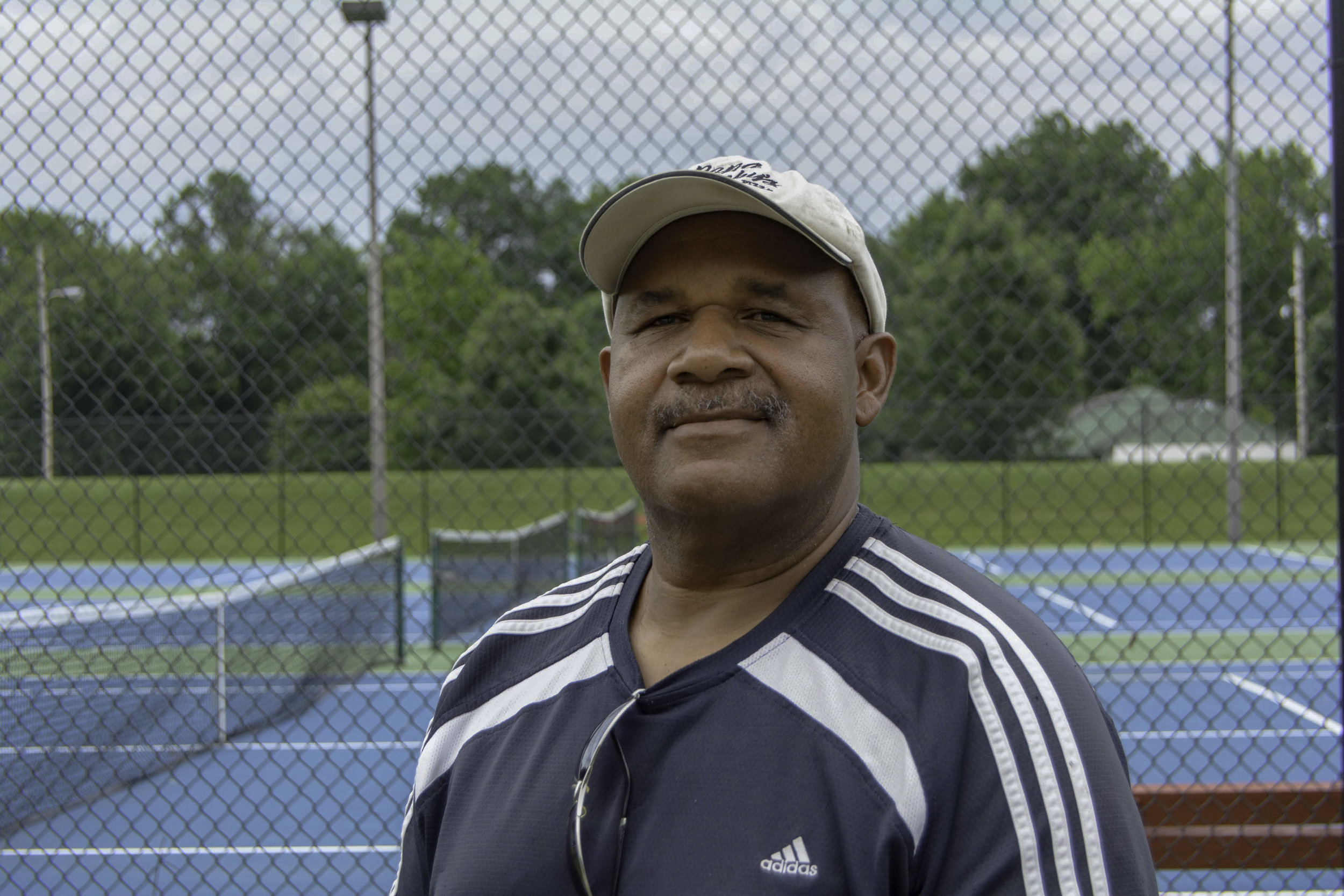 """""""I'm the director of the West Louisville Tennis Club. When we first had our opening day, we had about seventy parents and kids out here. Every Thursday at six o'clock, we have free tennis lessons. We're a non profit organization that plays tennis here and have been here for decades. We travel to different cities to play other clubs, too.  As of today, there are only two blacks who were inducted into the Kentucky Tennis Hall of Fame and that's Arthur Lloyd Johnson and my friend Bruce Stone. That's part of the legacy of the West Louisville Tennis Club.  I'm a certified tennis coach and I work for the United States Tennis Association. That's the same organization that pays Venus and Serena Williams. We have a chapter here called the USTA of Kentucky. I've been in different schools, targeting the areas that's not exposed to tennis. So, we've been to all of the West End schools trying to expose African American youth to tennis.  This is the home court for St. Francis and Central High School. It's been a decade since Central's had a tennis team, so it's been pretty good for the community. Hopefully, we can continue this venture with the community, exposing kids to another sport. Not only that, we're just trying to help raise kids in the community.  My brother, Frank, introduced me to tennis. He really got excited with Arthur Ashe won the Wimbledon in 1975. He went out and bought a couple of rackets and I didn't have a choice but to come out and play with him. He taught me how to play. That was in the mid-seventies and I've been playing ever since. As the years went by, I realized that it's one of those sports that you can play in your seventies and eighties. I had a cousin that played until he was 83 years old. It's one of those sports that gets under your skin and you can't help it. You can't play basketball and football forever.  We do a lot of fellowshipping and having fun out here. Plus, you get to stay in some type of shape. It's a lot of fun. We have tournaments whe"""