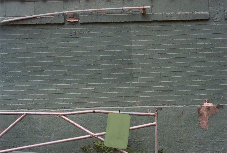 Erasure (green sign green wall metal fence)