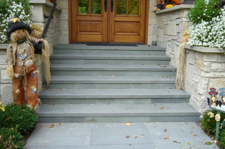 Entryway and Steps -  Highland Park, IL   A clean thermal bluestone with matching risers. This entry way was plain finished concrete. Here the homeowner wanted a clean natural look rather that man made concrete slabs. Set in slurry of concrete mix and proper sand, these bluestone steps have a long future.