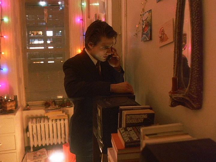 Cruise as Bill Harford in  Eyes Wide Shut  (1999); part of his reflection and half of a mask is visible in a mirror—a book under the mirror is entitled  Shadows on the Mirror
