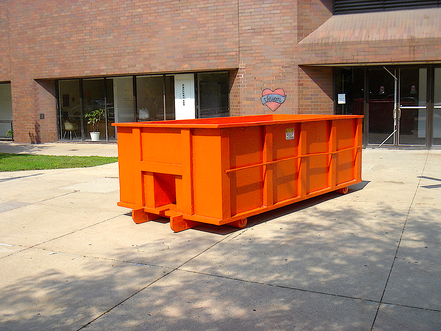 """Untitled Project: Dumpster  Enamel Paint on carved wood, 1:1 scale 2005   A carved and painted dumpster placed on the plaza in front of Gallery 400 at the University of Illinois at Chicago from September 2005 to February 2006. The dumpster sculpture functioned in many ways like a real dumpster in that it was both a visual symbol for construction/renovation/change and a platform for participation. During its brief stay, it collected trash, became a sifting site for recyclables, a support for student artworks and interventions, and a surface for graffiti–which in turn was painted over by the city of Chicago's graffiti removal program. In the end the dumpster was emptied and delivered to Dan Peterman's experimental station, which was then under (re)construction and needed a """"dumpster"""" to comply with city code."""