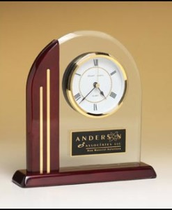 "Arch Table Clock   Arch clock with glass upright and rosewood piano-finish post and base. Price of $103.00 does not include engraving. Engraving is the greater of $24 or 30¢ per character. Overall size is 7½"" x 7-7/8″ x 2″.  Lifetime guaranteed movement ."