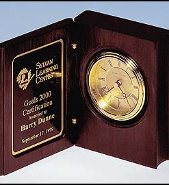 "Book Clock   Rosewood stained clock in the shape of a book. Diamond spun dial and 3 hand movement that is guaranteed for life. Price of $87.50 does not include engraving. Engraving is the greater of $24 or 30¢ per character. Overall size is 5 3/8″ x 4¼"" x 1 7/8″."