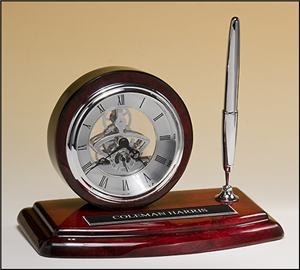 Skeleton Desk Clock   Skeleton clock with sub-second dial, silver movement and pen on rosewood piano-finish base. Price of $172.00 does not include engraving. Engraving is the greater of $24 or 30¢ per character. Overall size is 8.25 x 5″.  Lifetime guaranteed movement