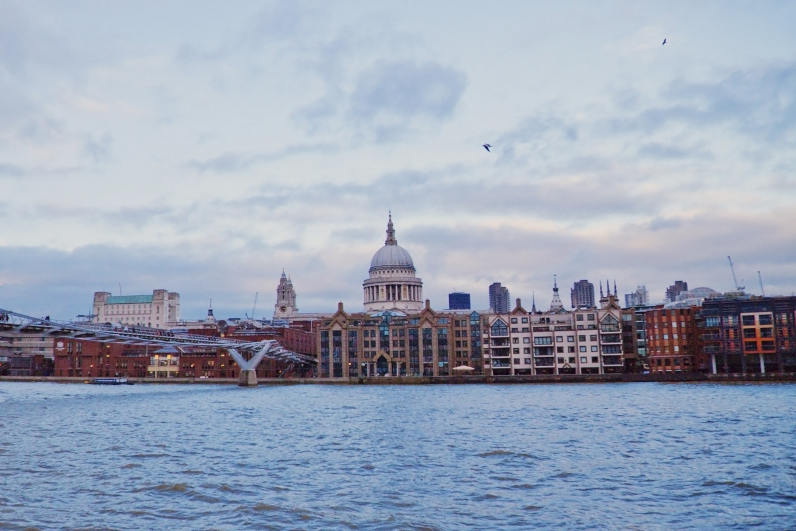 Millennium Bridge + St. Paul's Cathedral popping up over some buildings