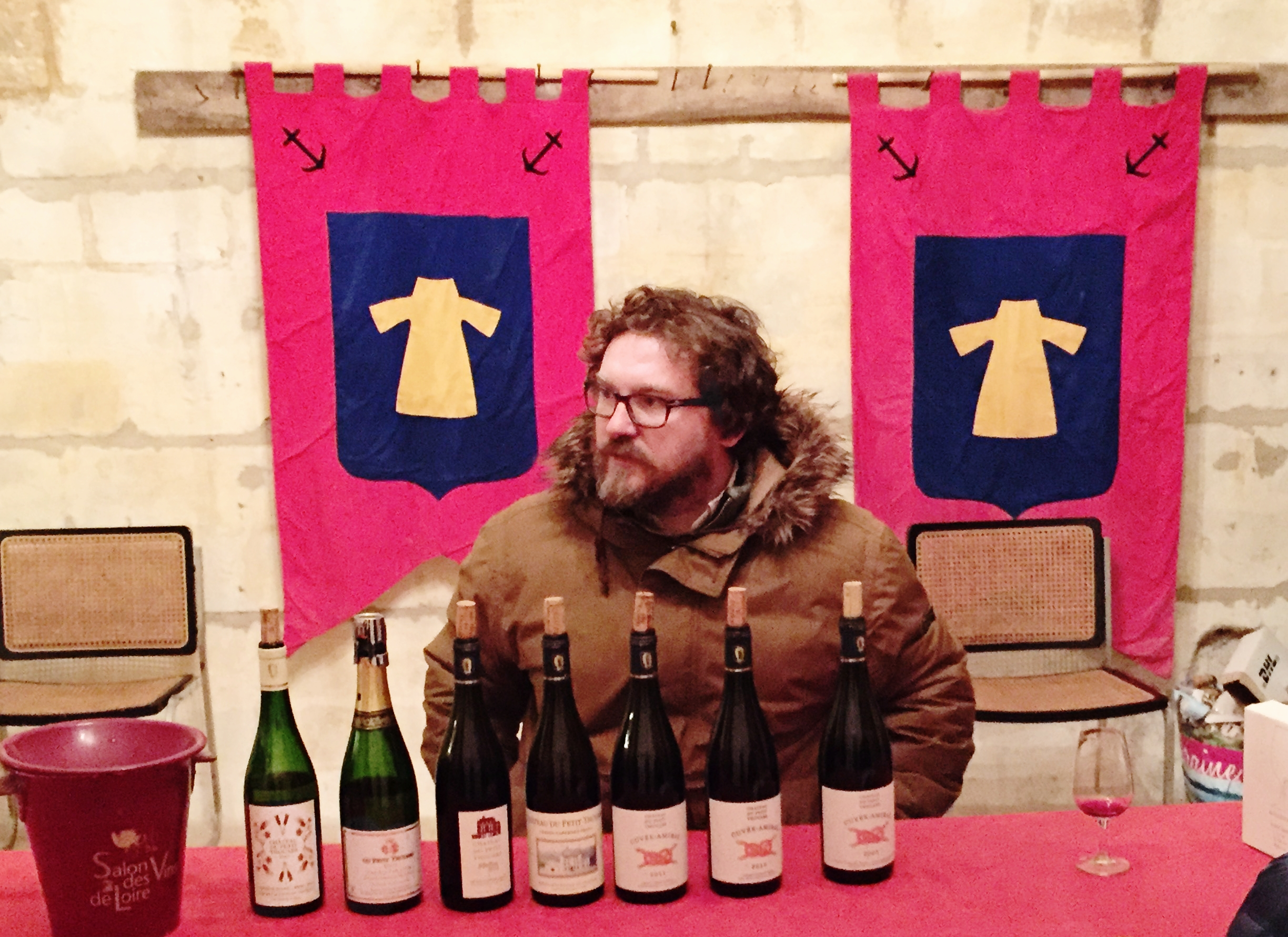 Sébastien pouring us his wines in front of flags with his family crest.