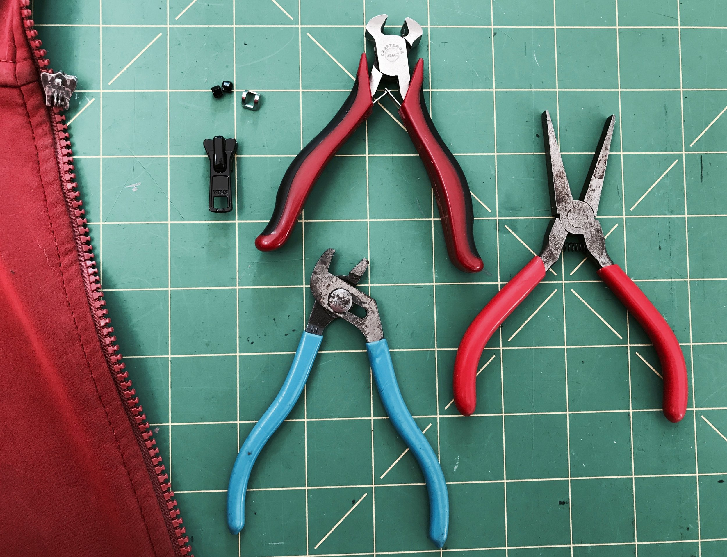 Tools of the trade. Replacement end stops, replacement zipper slider, small end nippers, small channel lock pliers and optional flat needle nose pliers. The whole job can be done with a multi-tool in the field, though these tools do make it a bit easier. Note the various end stops in the upper left of the picture. various sizes and styles are available.