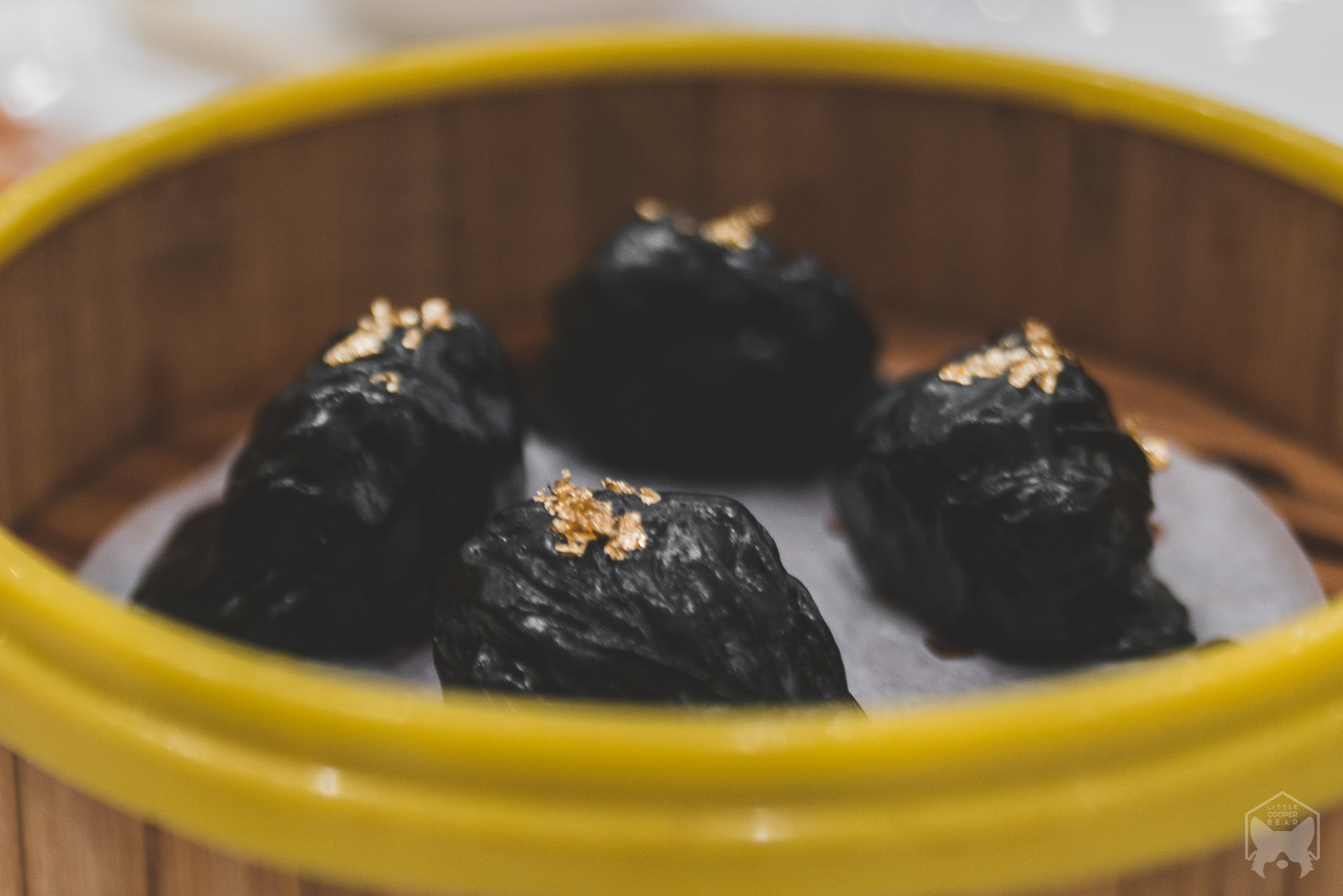 Squid ink har gao with gold flakes
