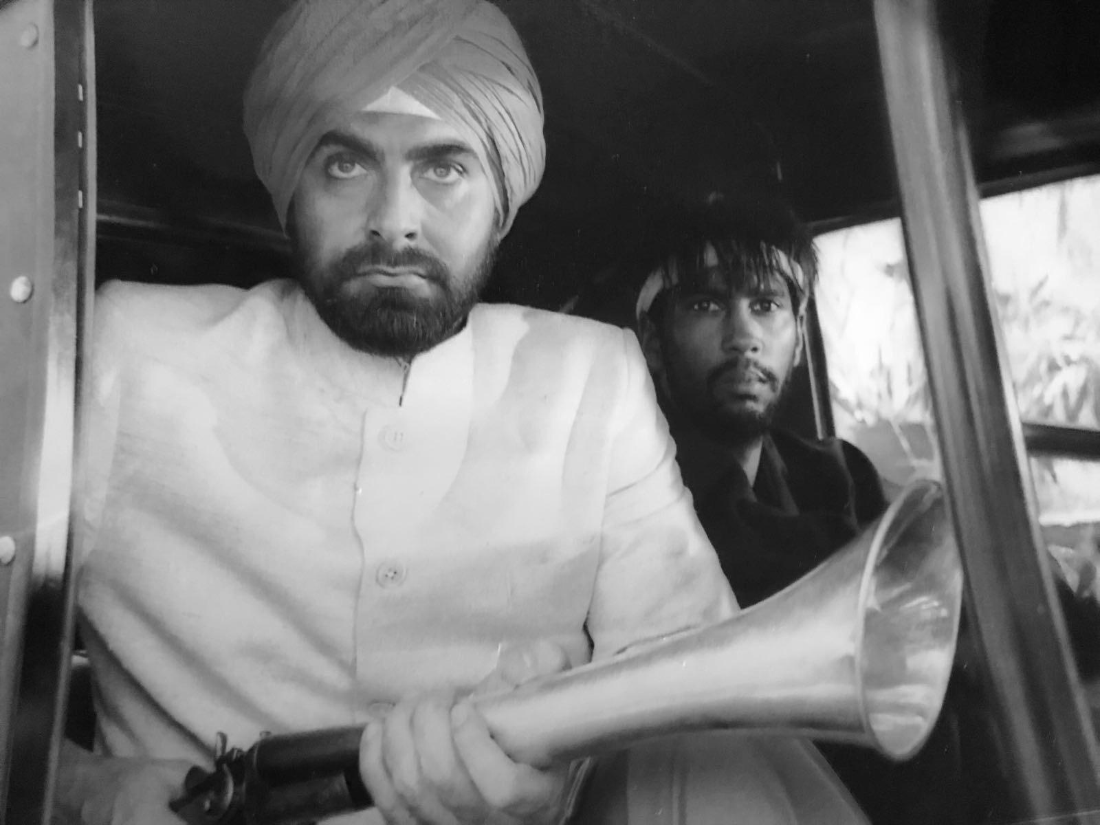 Kabir Beid and Michael Moor waiting for Roger Moore in Octopussy. Watch the scene below.