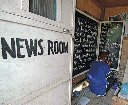 Alfred Sirleaf writes the day's major headlines on a blackboard for Liberians who cannot afford newspapers.