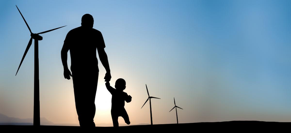 energy-renewable-man-and-baby-walking-toward-wind-turbines.jpg