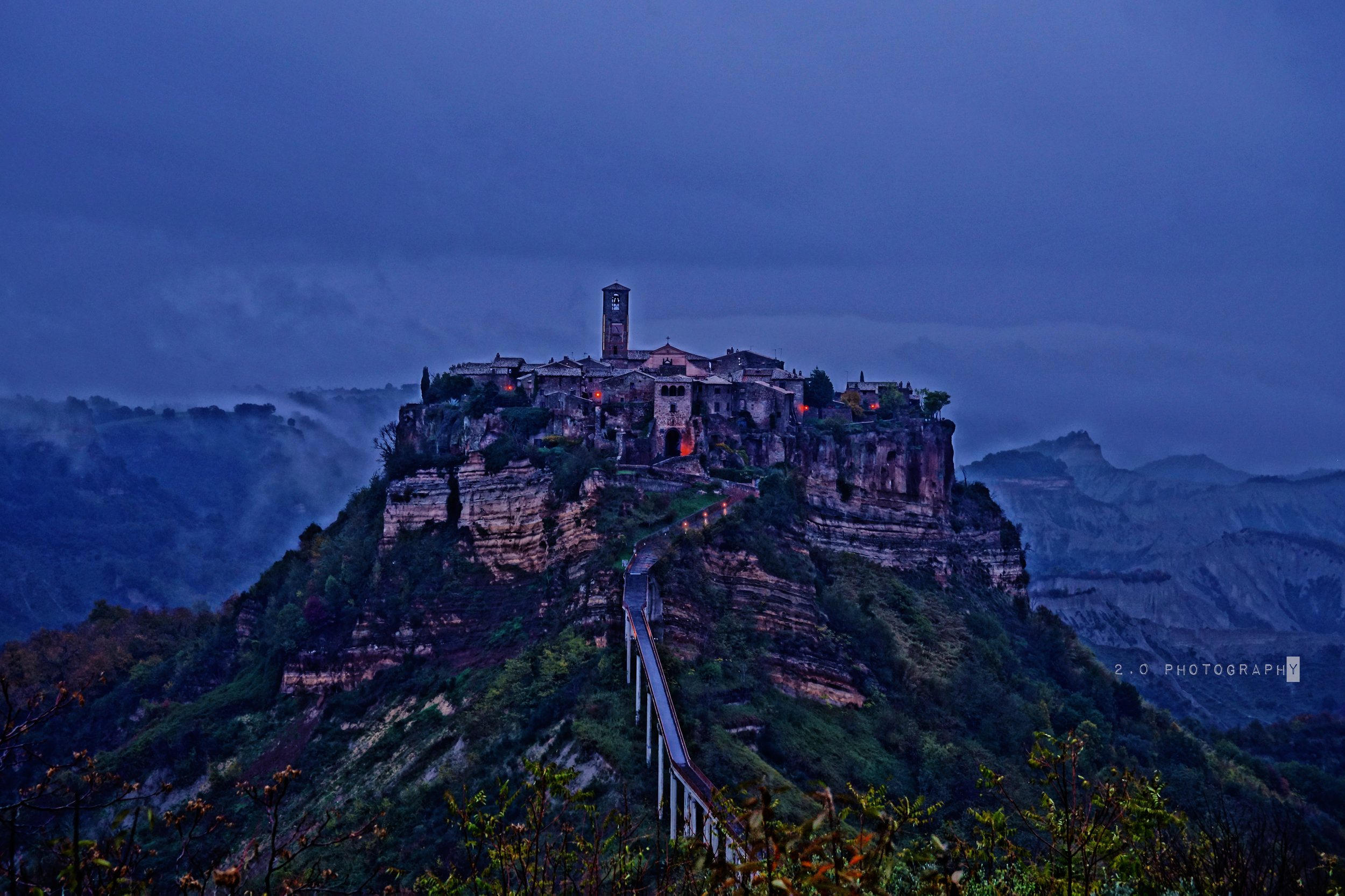 "Civita di Bagnoregio  (il paese che muore, 'the town that is dying"") - Located in the Vitero Province in central Italy, Citiva resides as a suburb of Bagnoregio. Citiva was founded over 2,500 years ago by ancient Italy's Etruscans. In the 16th century, Citiva began to decline as it was eclipsed by Bangoregio. Earthquakes accelerated the city's decline during the 17th century, and by the 19th century, Citiva was turning into an island. Citvia and its inhabitants are in constant danger of being washed into the sea, as the edges of its plateau succumbs to erosion. Buildings crumble as their underlying support falls away, a fact that is truly heartbreaking. This city's architecture spans several hundred years, and, perhaps because of this fact, has been experiencing a tourist revival. In 2004, there were plans to reinforce the island city's plateau with steel rods to prevent further geological damage from occurring.https://en.wikipedia.org/wiki/Civita_di_Bagnoregio"