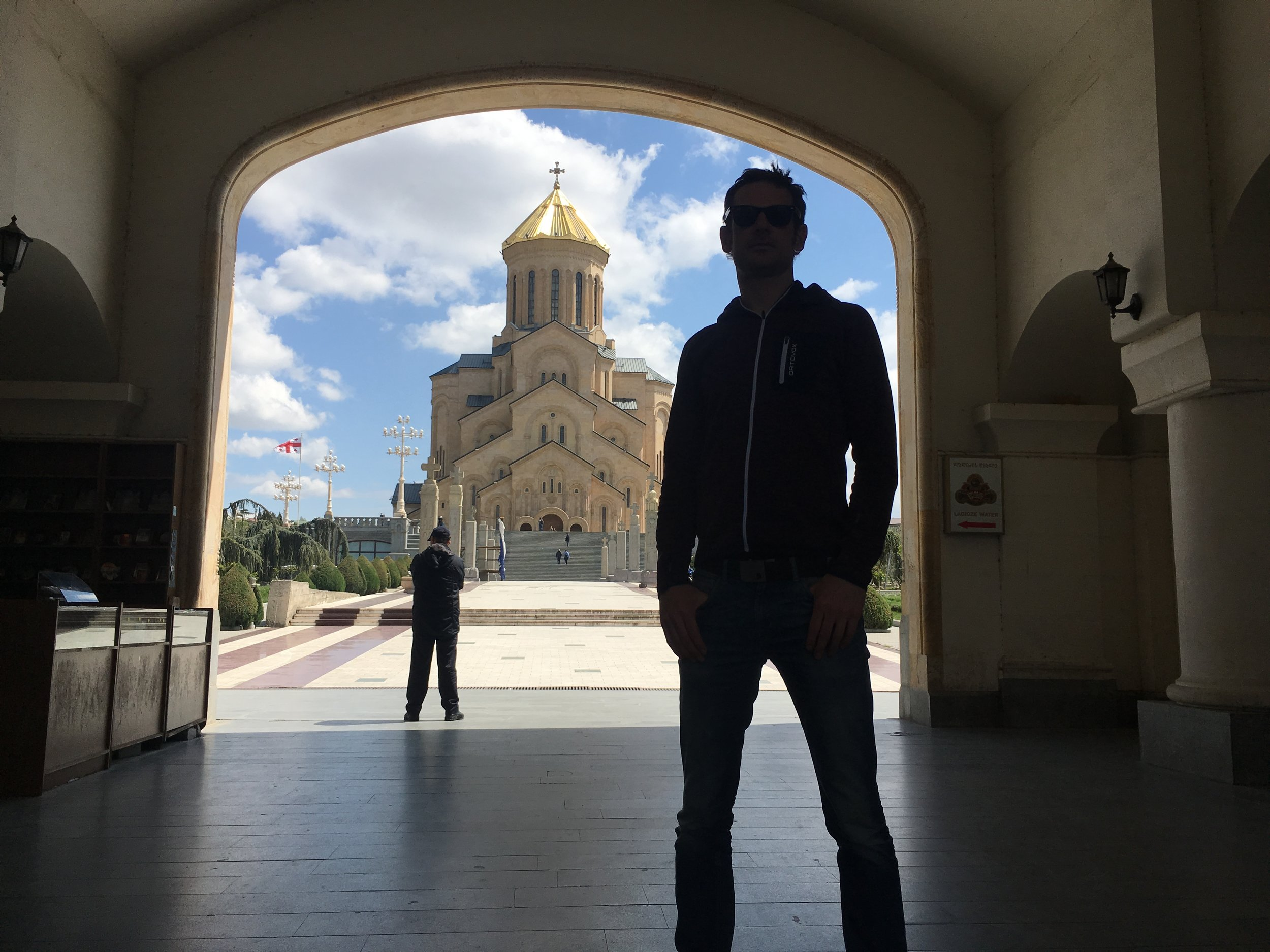 The trinity of the Holy Trinity Cathedral of Tbilisi, a security man and Thies.