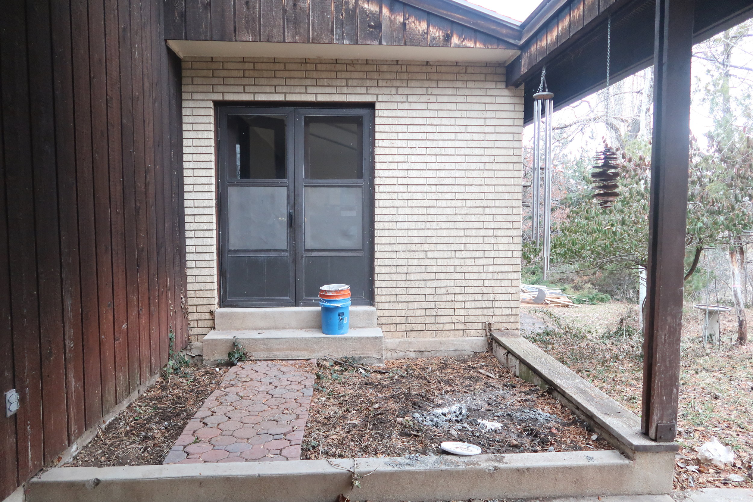 Rear covered patio now. We plan to stain the exterior wood paneling, plant new flowers and greenery and eventually replace the existing door.