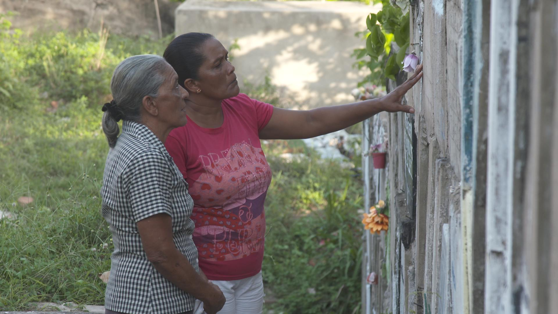 Dilia with Maribel visiting the graves of her children