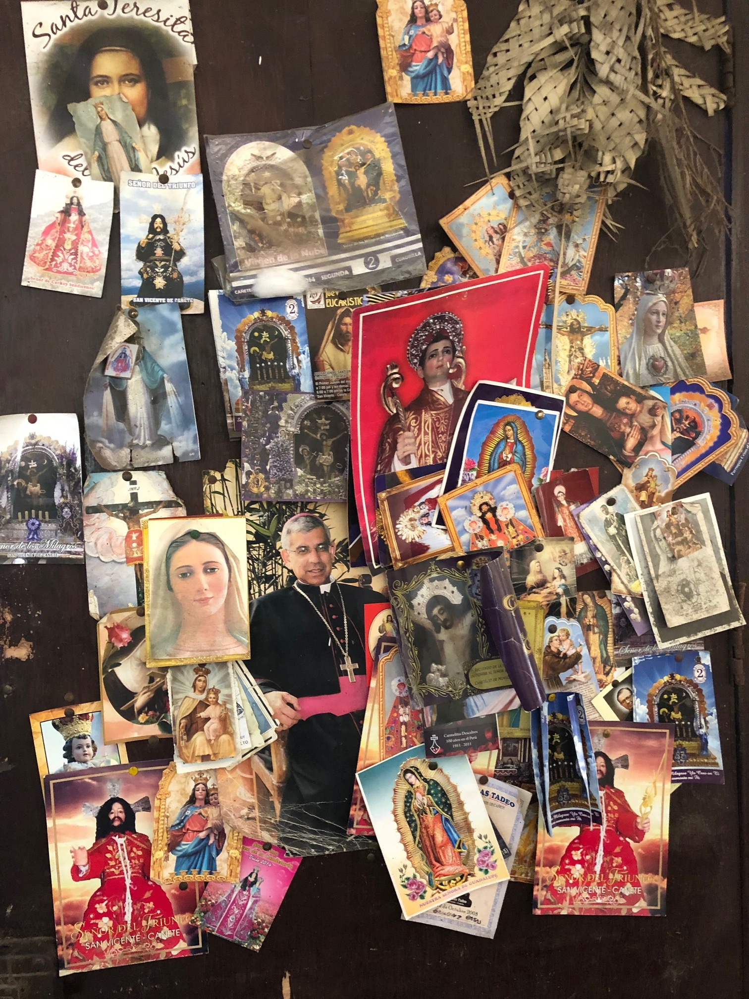 A door of a family home filled with religious images. Families are very religious and expect more help from their Church
