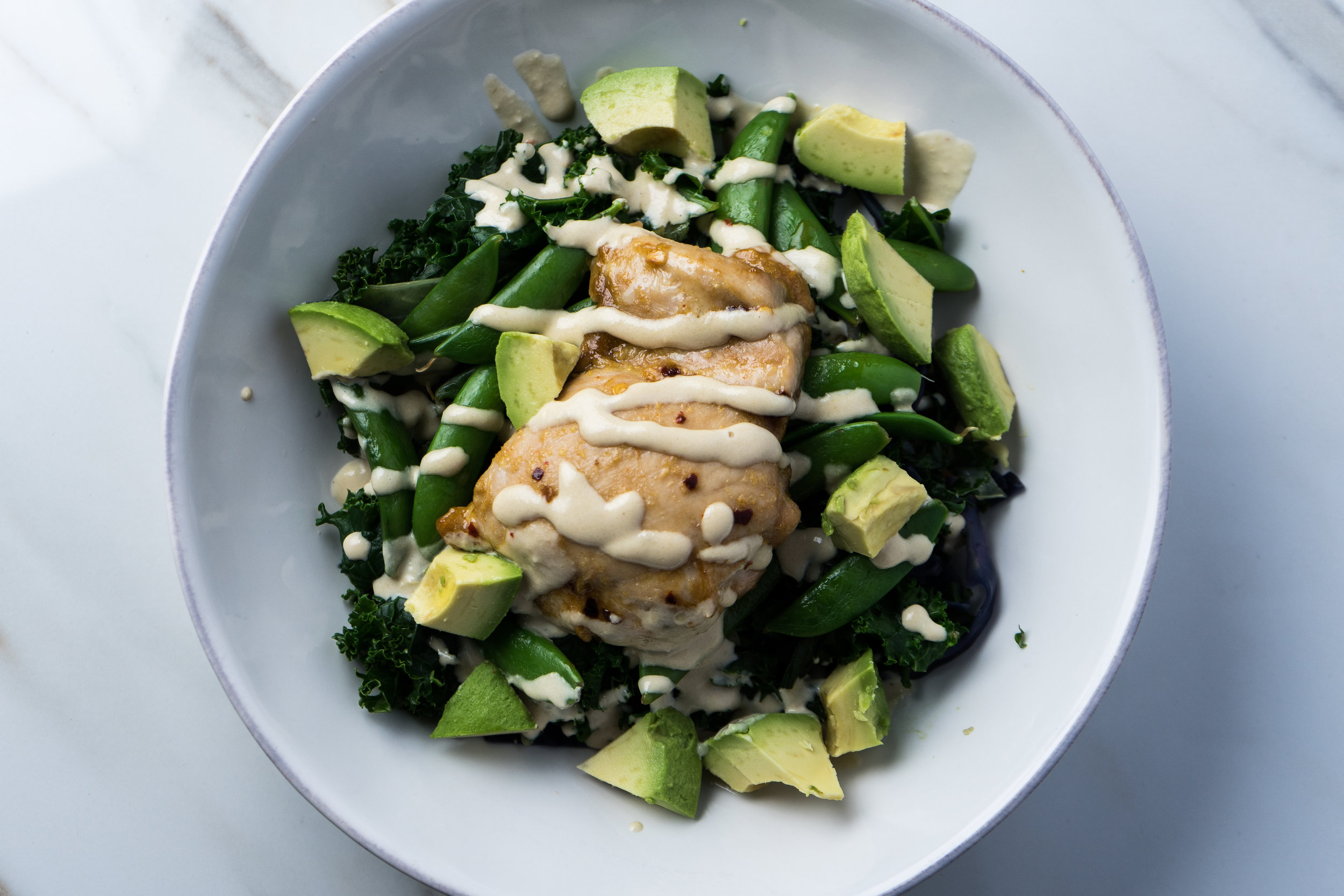 Steamed curly kale, sautéed snap peas, baked asian chicken, avocado and miso tahini drizzle.