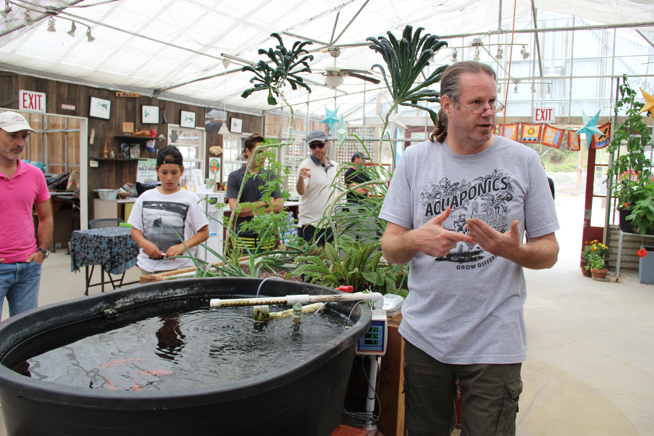Ken Armstrong, founder of Ouroboros Farms, demonstrating a home aquaponic system.
