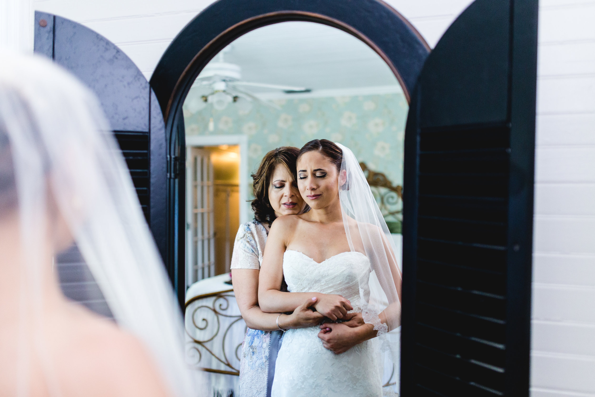 A wedding, engagement, love, newlywed image of of a bride embracing her mother-taken by Miami Wedding Photographer, Javier Edwards of El Roi Photo, in Miami, Florida.