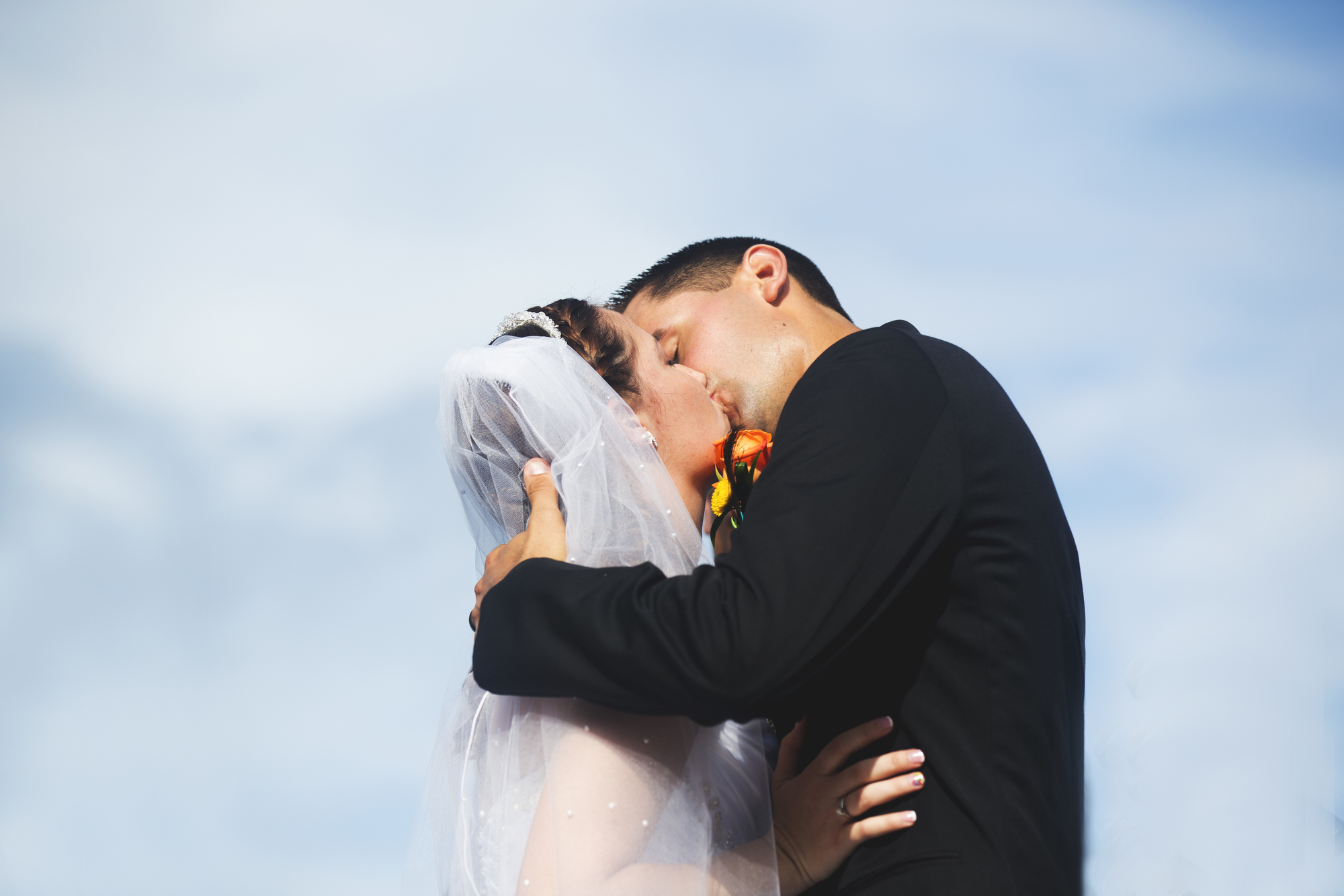 A wedding, engagement, love, newlywed image of a bride in her wedding dress, kissing the groom -taken by Miami Wedding Photographer, Javier Edwards of El Roi Photo, in Miami, Florida, for a Miami Wedding